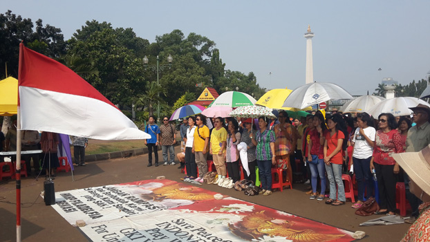 Jemaat menyanyikan lagu Indonesia Raya seusai ibadah, Minggu (21/6)
