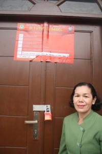 Pdt. darna Lumban Tobing di depan pintu gereja yang telah disegel