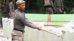 Seorang Satpol PP menghancurkan dinding gereja dengan palu